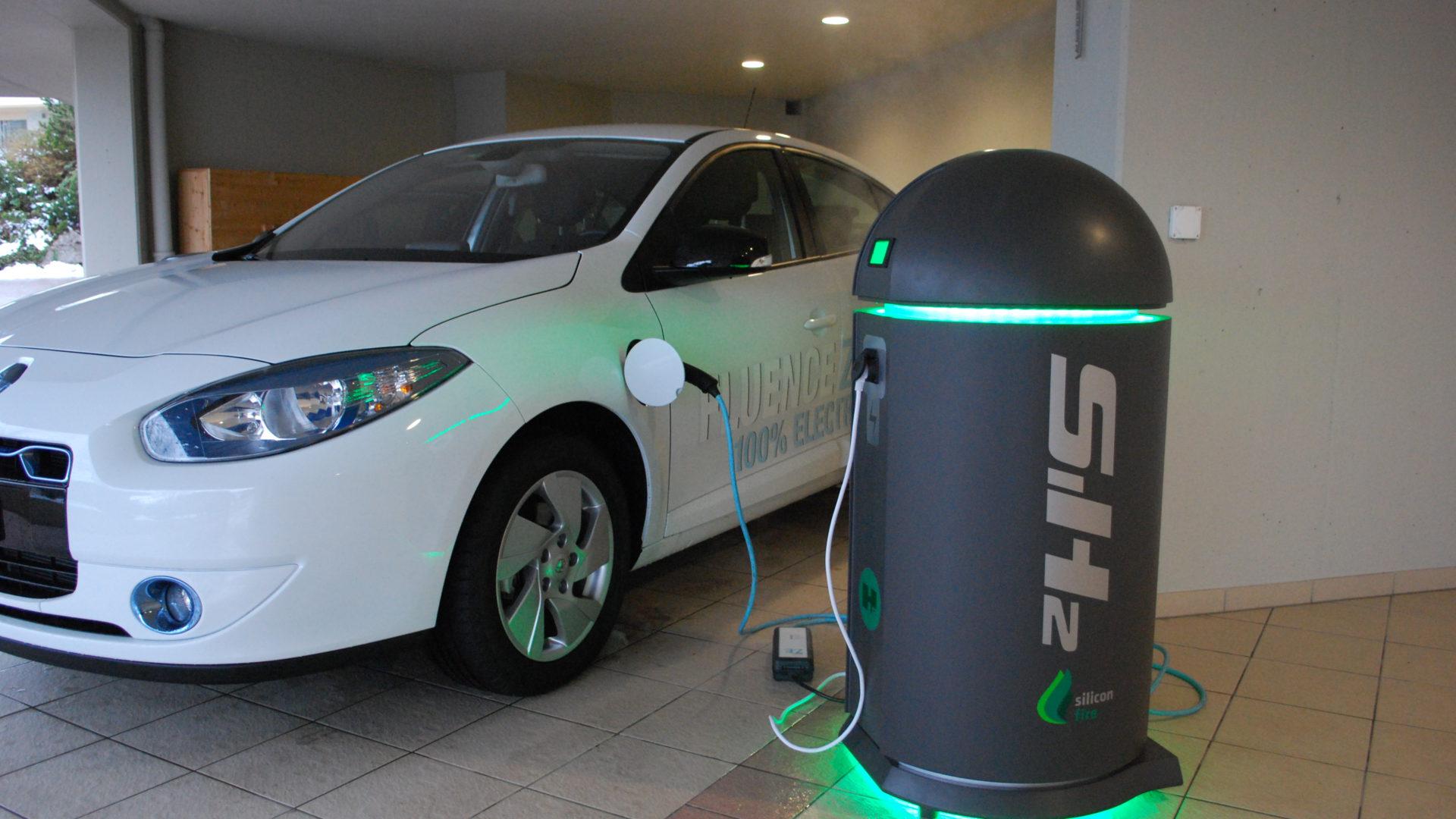 Silicon Fire SiH2 Ladestation mit einem an sie angeschlossenen Auto.