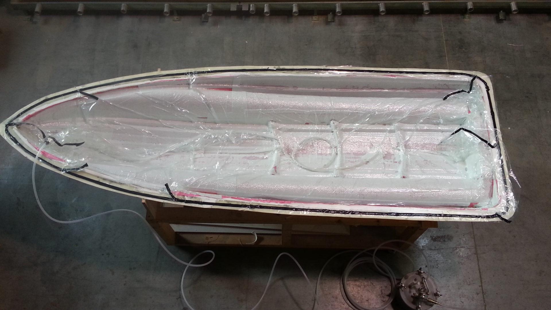 Produktion eines Bootes von FELLERyachting. Die Ansicht ist von oben herab. Zu sehen ist ein Bootsrumpf während eine Infusion mit Epoxydharz statt findet.
