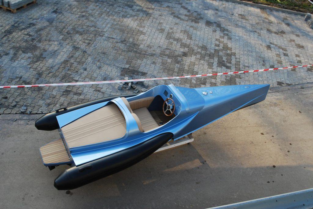 Elektroboot FELLERyachting, blau lackiert, beigefarbene Innenausstattung und vorne spitz zulaufend.