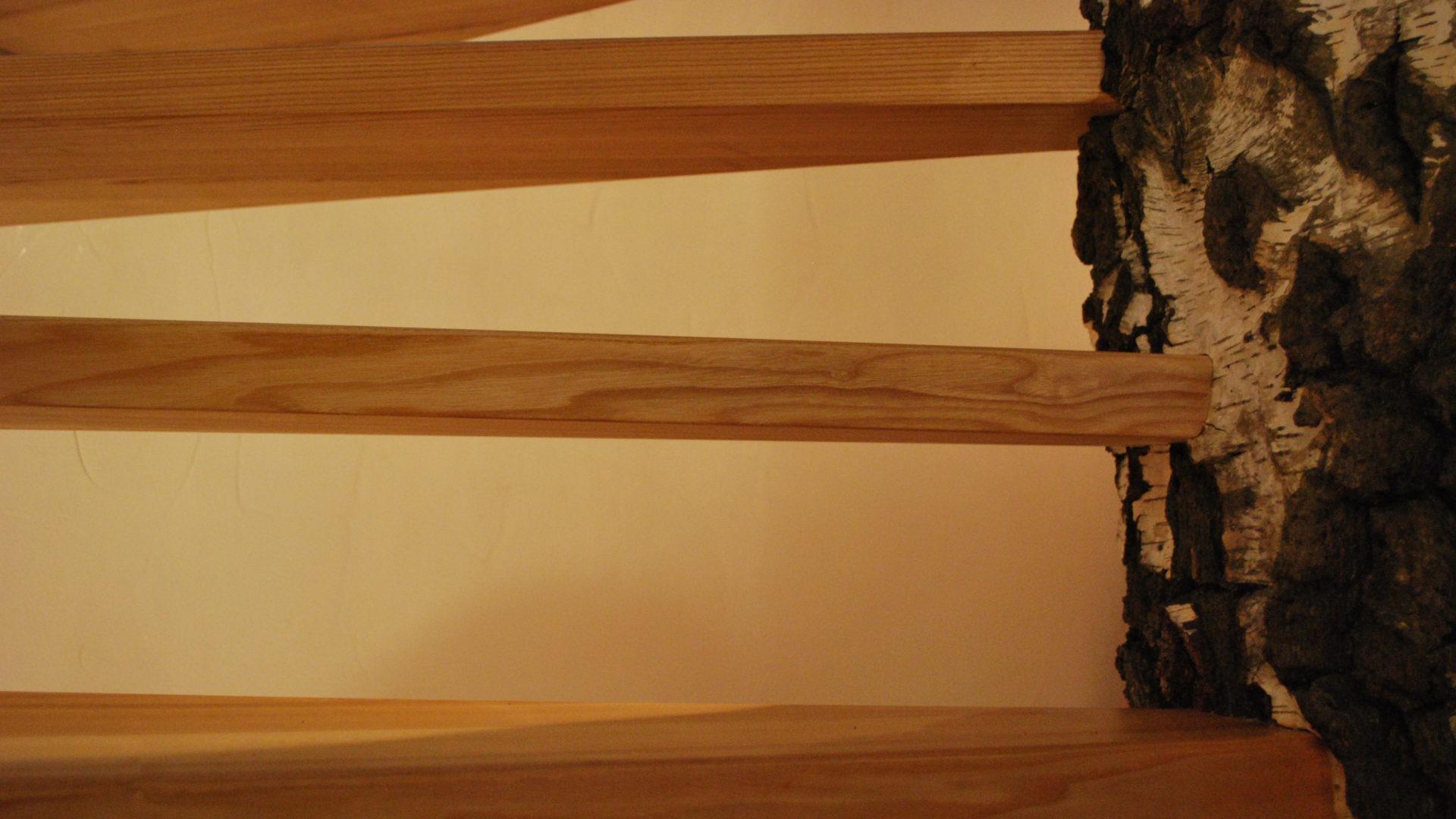 Detailansicht einer Wendeltreppe, die sich um einen noch ganzen Baumstamm mit Rinde windet.