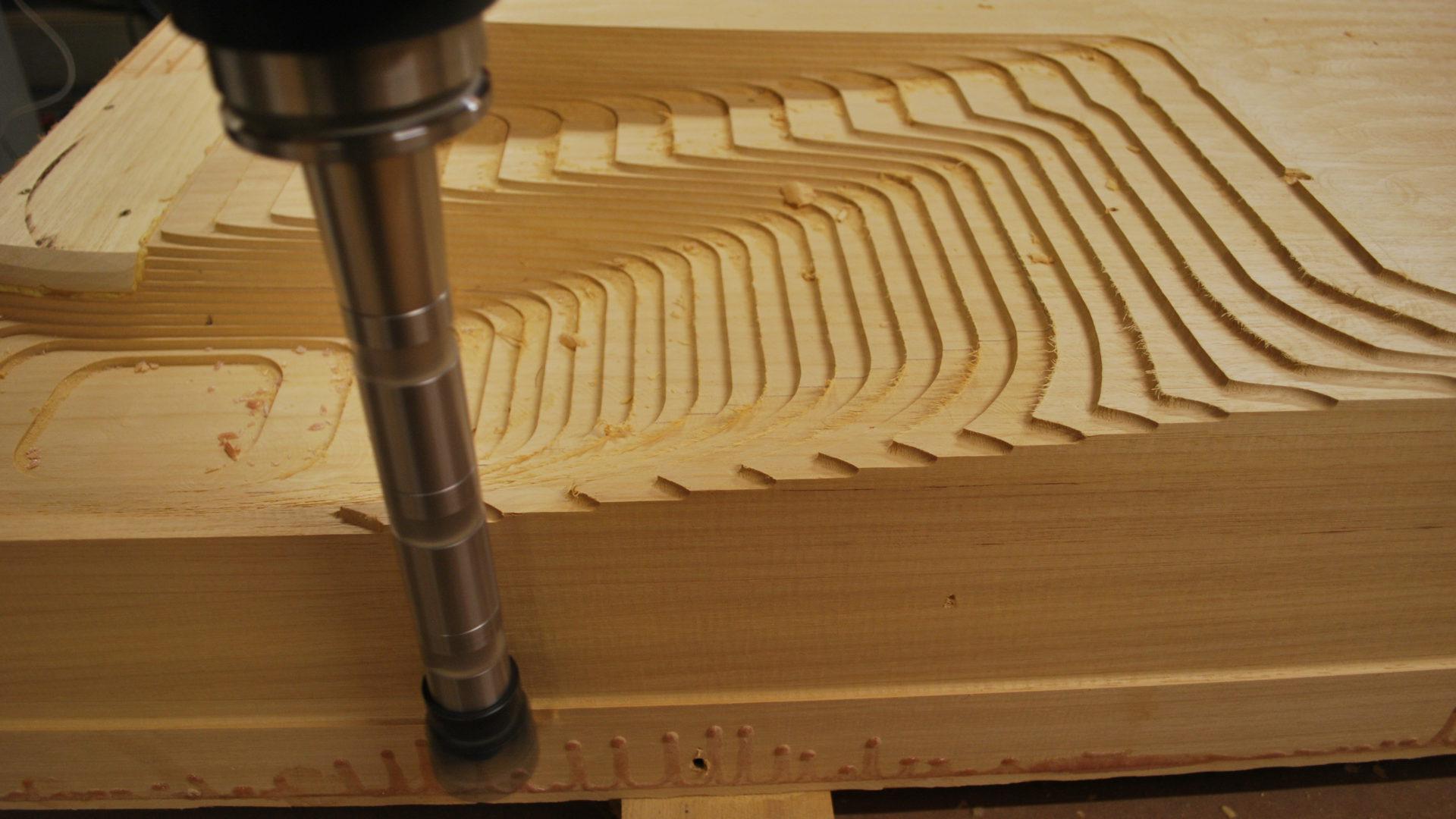 Detailansicht des KUKA KR 210 Roboter beim Fräsen eines Holzmodells. Seitenansicht.