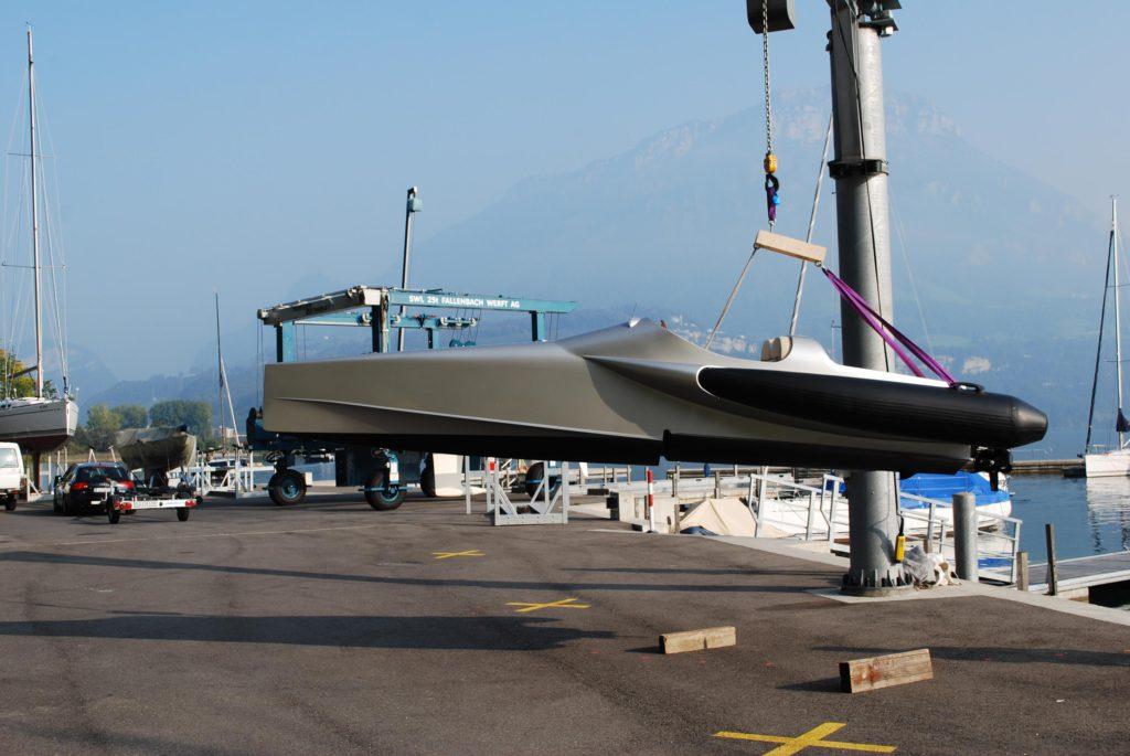 Sportboot FELLERyachting, mit 100% Methanol betrieben. Silbergrau lackiert und vorne spitz zulaufend. Hier hängt es an einem Kran am Rande eines Piers.