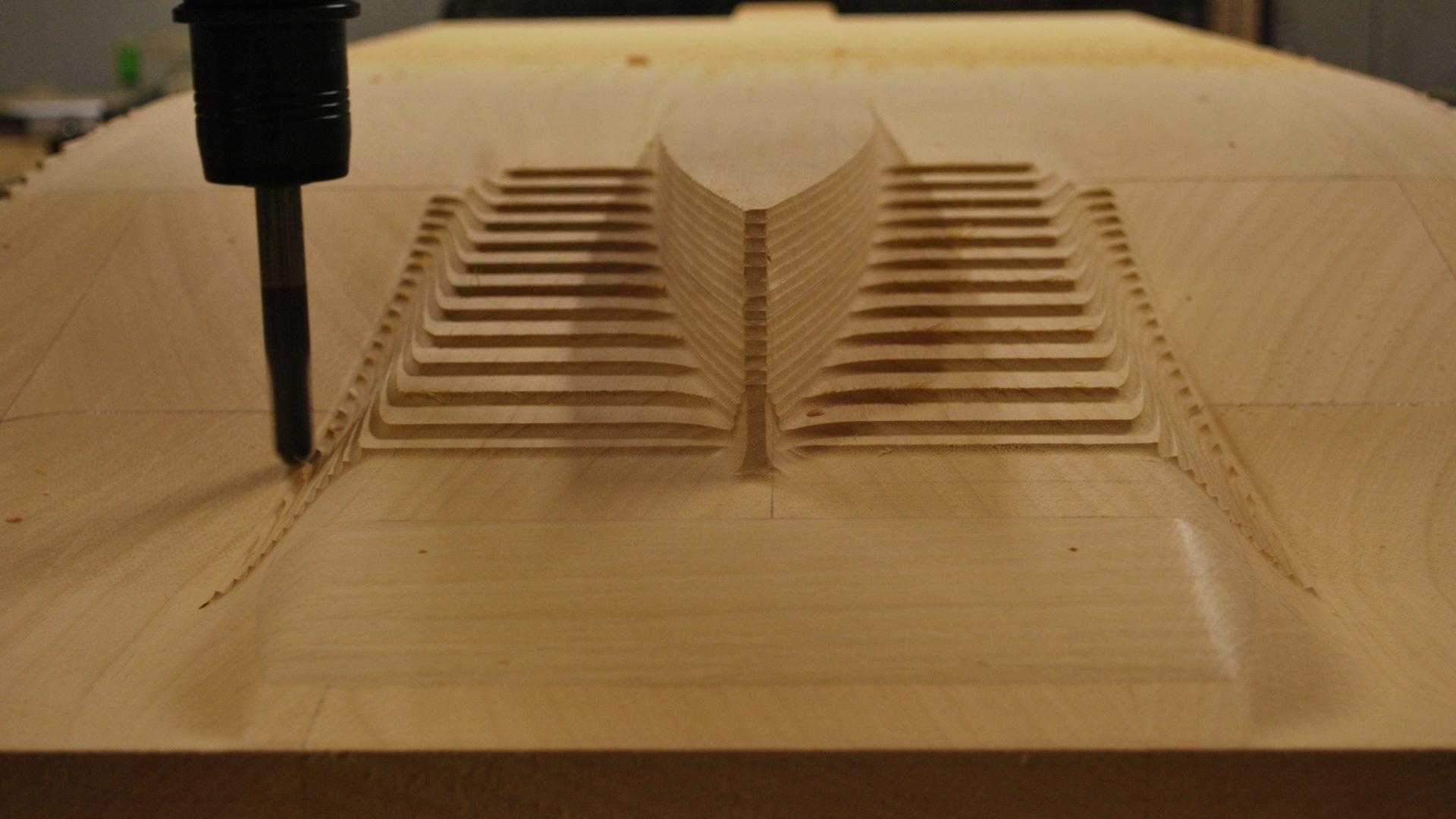 Detailansicht des KUKA KR 210 Roboter beim Fräsen eines Holzmodells.