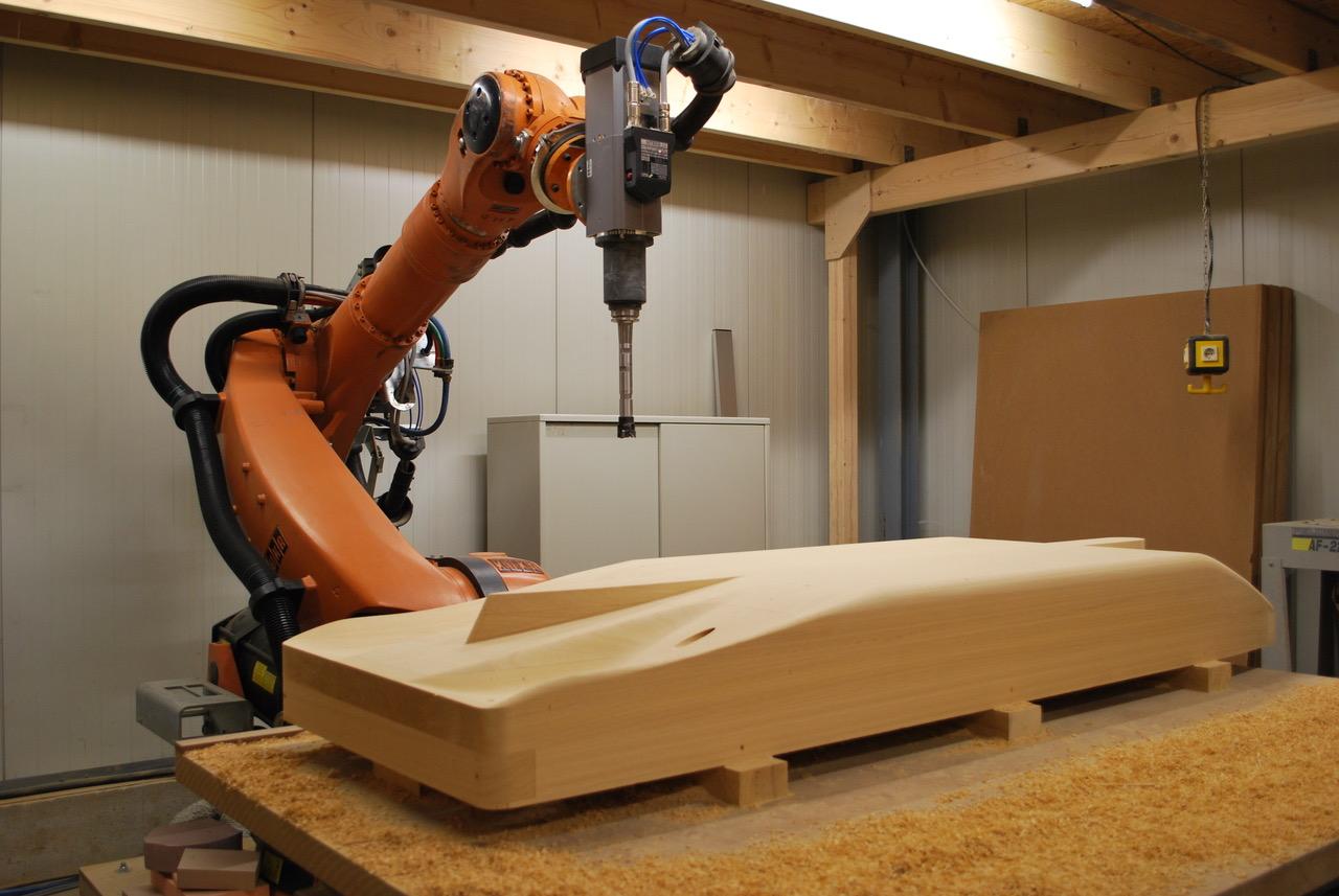 Umgebauter KUKA KR 210 Roboter mit sechs Achsen, unglaublich beweglich und mit einem großen Arbeitsbereich. Hier auf dem Bild zu sehen zusammen mit einem gefrästen Holzmodell.